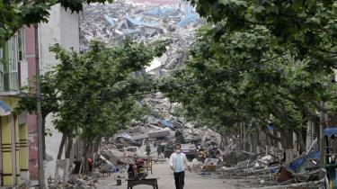 I baggrunden ses en bakke med en kolossal bunke ruiner i Mianyangs gamle bydel og overlevende leder i brokkerne øverst til venstre. Det massive jordskælv i mandags har måske kostet 50.000 livet. Tusindvis frygtes begravet levende under de sammenstyrtede huse.