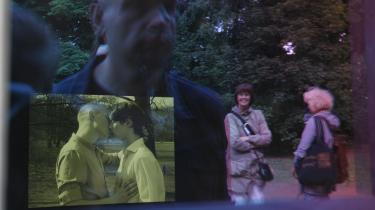 Kigger man ind i vinduet på mindesmærket for nazi-Tysklands homoseksuelle ofre, ser man en film med to mænd, der giver hinanden et kys. Her spejles gæster ved indvielsen af mindesmærket i vinduets glas.
