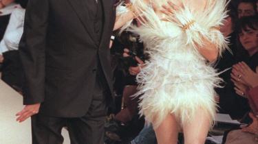 Yves Saint Laurent på catwalken sammen med supermodellen Laetitia Casta i en hvid kjole, der udelukkende består af fjer.