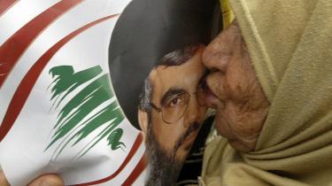 En libanesisk kvinde trykker et kys mod en plakat af Hizbollah-lederen Hassan Nasrallah, der har stor opbakning fra libaneserne efter at han med et på disse kanter ekstraordinært talent for organisering har fået skoler, klinikker, børnehjem, boliger, broer og præsteskoler op at stå.