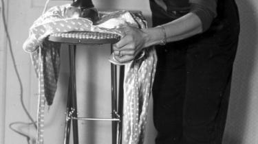 En dansk husmor i 50-ernes Danmark i gang med de hjemlige pligter. Ifølge direktør for KVINFO Elisabeth Møller Jensen er de unge kvinder på det danske arbejdsmarked banket tilbage til 1950-ernes kønsroller af regeringens egen politik på barselsområdet.