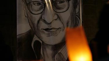 Stearinlys brænder ved siden af en plakat af den store palæstinensiske digter Mahmoud Darwish i Rahmallah forleden. Darwish fik i går en såkaldt 'statsbegravelse'; en ære, der tidligere kun er overgået PLO-lederen Yasser Arafat.