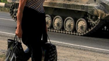 Georgiens fremtidige NATO-medlemsskab afhænger af en varig løsning på konflikterne med udbryderregionerne Abkhasien og Sydossetien. Men det bliver ikke nødvendigvis med nuværende præsident Saakashvili ved roret, idet den manglende håndtering af de store flygtningestrømme mod hovedstaden Tbilisi kan give ham alvorlige problemer. Her ses en flygtning på vej ud af byen Gori i det østlige Georgien, mens russiske kampvogne kører forbi.