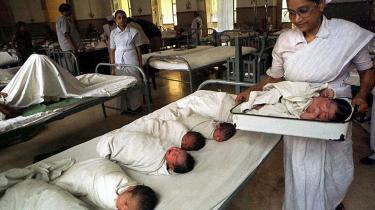 En sygeplejerske med et nyfødt barn på et hospital i Calcutta. Andre hospitaler i Indien tager sig også af fødsler foretaget af rugemødre. Siden 2002 har det været fuldt lovligt at hyre en rugemor i Indien, og det har fået industrien til at boome.