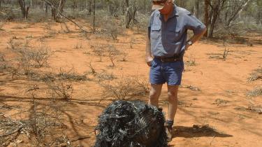 En mand fra Queensland kigger på et stykke rumskrot, der er faldet ned fra oven. Men faldende himmelobjekter er angive-ligt ikke den vigtigste årsag til, at kvinderne flygter fra Queensland-byen Mount Isa.