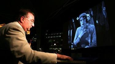 Live. Jeg tager dramatiske beslutninger undervejs, beslutninger om det, der foregår mellem linierne i en scene, siger Neil Brand, der er uddannet skuespiller, men har akkompagneret stumfilm i mere end 25 år.