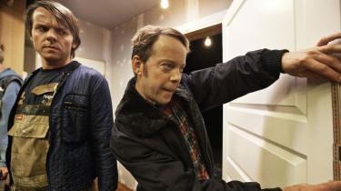 Søren Sætter-Lassen (th.) glimrer i rollen som håndværksmesteren Glen, der spiller et udspekuleret dobbeltspil med sine arbejdsgivere. Her mistroisk overvåget af Halvbror, spillet af Niels-Martin Eriksen.