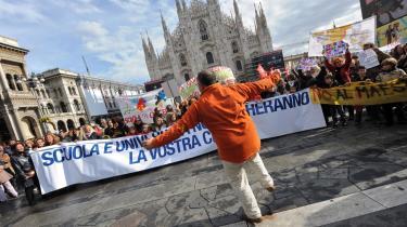 En lærer danser foran et banner med ordlyden: -Skole og universitet vil ikke betale for jeres krise-. Hundredevis af lærere, elever og forældre demonstrerede mod Berlusconis milliard-spareplan på skole- og universitetsområdet.