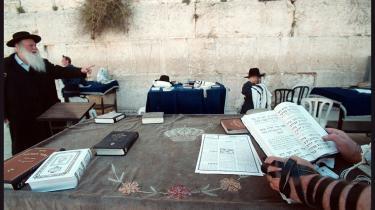 På begge sider af Jerusalems både synlige og usynlige demarkationslinjer vokser spændingerne med de ny-fundamentalistiske strømninger som mental spagnum, og selvbestaltede kontrollanter holder øje med, at de religiøse krav til -moderat påklædning og optræden- ikke krænkes. På billedet ses ortodokse jøder ved Grædemuren.