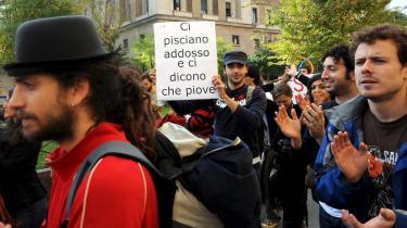 -De pisser os ned ad ryggen, og siger det regner-, står der på den unge demonstrants skilt om regeringen. De italienske studerende har været massivt på gaderne de sidste uger pga. Berlusconis privatiserings- og brugerbetalingsplan.