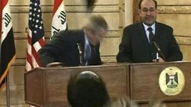Bush dukker sig promte, da to sko lynhurtigt efter hinanden fløj målrettet i retning af hans hoved på pressemødet i Bagdad. Kasteren mente, at nu var det nok med Bush og USA-s ulykker i Irak.