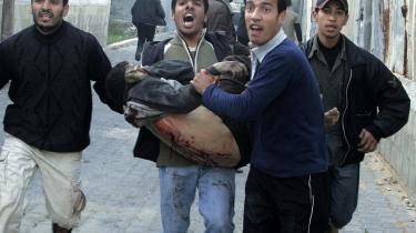 En palæstinenser, såret ved angrebet på en FN-skole i Gazastriben i går, bæres væk fra de sønderbombede bygninger. Omkring 40 personer blev såret.