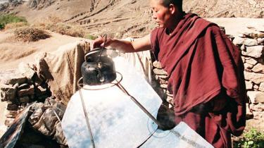 En tibetansk munk koger en kedel vand takket være en solenergi-kogeplade. Solenergipladen er lavet i Sichuan i Kina, som nu er ramt af CO2-markedets sammenbrud.
