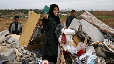 En palæstinensisk kvinde holder sit id-kort frem, efter at hun fandt det i den bunke af betonbrokker og møbler, der udgør hende og familiens tidligere hjem i den sydlige del af Gaza By.