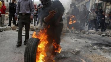 En Hamastilhænger sætter ild til et dæk i forbindelse med en demonstration i byen Hebron på Vestbredden. Med Israels undertrykkelse og omverdens passivitet er det måske ikke så underligt, at Hamas har fået en stor folkelig opbakning.