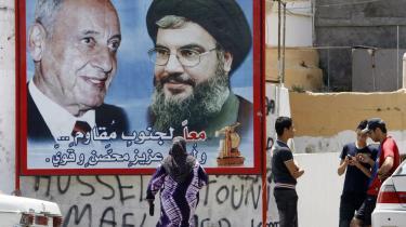 Indviklet. En håndfuld knægte synes mere optaget af at holde sms-kontakt med vennerne end af at tage notits af billboardets smilende udgaver af parlamentsmedlem Nabih Berri og Hezbollah-lederen Hassan Nasrallah (th). Men libanesisk politik er også meget indviklet, lyder en af de lokale vurderinger op til valget.