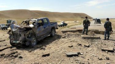 Dagens vejsidebombe - Afghansk politi besigtiger et køretøj, som blev totalt ødelagt af en kraftig bombe gemt under vejbelægningen ved byen Kunduz i går, og de fire afghanske nødhjælpsarbejdere i bilen blev såret, men overlevede.