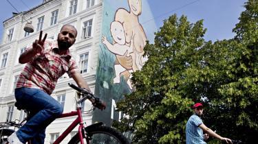 Dansk frisind.  To unge mænd cykler forbi et par mælkeholdige bryster på kapelvej, Nørrebro.