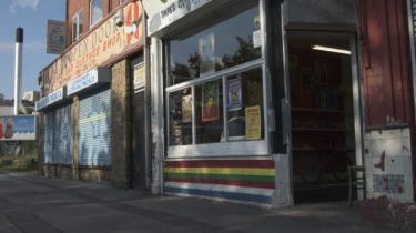 Nedrullede skodder og falmede butiksfacader i hvert tredje vindue på Princess Road vidner om, at bandefejden har været hård ved forretningslivet  i Moss Side.