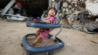 En lille palæstinensisk pige i sin mobile kravlegård lige foran sin families totalt udbombede hus, der blev ødelagt under Israels 22 dage lange bombardement af det nordlige Gaza i år i januar. Halvdelen af de civile dræbte i Gaza var civile, mener en israelsk organisatiopn.