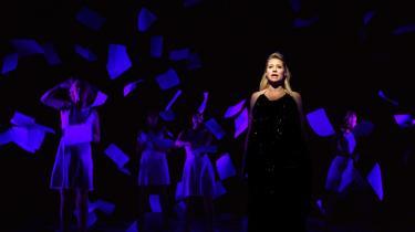 Smukke, sexede Trine Dyrholm glimter i sorte divapailletter mod sine papirarksdansere i 'Baby Blue'. Men Steffen Brandt står lige nede i orkestergraven og bevogter hende med sin guitar.