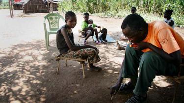 Penina Abiriba Sylavan (tv.) slap væk fra Lords Resistance Army efter at have været kidnappet og forsøgt dræbt. Fire af hendes  søskende er stadig taget til fange. Her er hun sammen med sin familie, der er flygtet fra deres hjemby på grund af LRA.