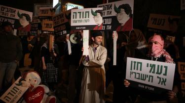 Demonstranter har protesteret foran Naomi Chazans - formand for New Israel-fonden - hus med skilte med en karikatur af hende med horn i panden.