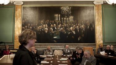 Forrest videnskabsminister Charlotte Sahl-Madsen (K) i Videnskabernes Selskab. Bag nutidens videnskabelige samfundselite sidder 1890'ernes videnselite i form af et enormt Krøyer-maleri, der pryder hele bagvæggen i den imposante plenarsal.