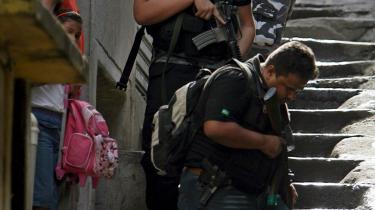Betjente på jagt efter narkohandlere i Alemao-favelaen i Rio de Janeiro. Den nye strategi i kampen mod banderne er permanent besættelse af ghetto-områderne.
