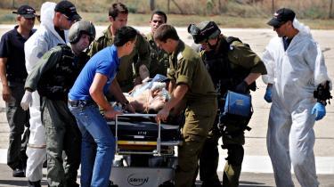 En såret mand fragtes væk og får behandling efter at have været under beskydning om bord på nødhjælpskonvojen.
