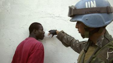 En brasiliansk FN-soldat giver et mistænkt bandemedlem vand under en patrulje i Port-au-Prince. FN-styrkerne og sociale aktiveringsprogrammer har haft held med at begrænse banderne i Haitis hovedstad, men høj arbejdsløshed og en ophidset politisk situation kan nemt genoplive dem, frygter observatører.