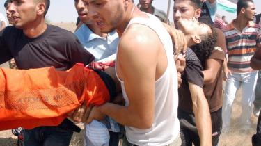 Under en demonstration   i går mod den israelske   blokade i det sydlige Gaza   bærer palæstinensere   en såret mand væk.