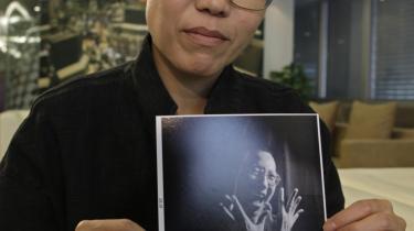 'Denne pris er til alle dissidenter, der som Liu Xiaobo stadig er i fængsel,' sagde   Liu Xia i går. Hun viser her et fotografi af sin fængslede mand, der i går fik Nobels fredspris.