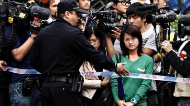 En kinesisk politimand taler med journalister, mens de kinesiske myndigheder spærrer vejen ind til Liu Xiaobos kones hus. Kinas statskontrollerede medier er fulde af foragt over at Liu Xiaobo har fået Nobels fredspris, samtidigt med at landet forsøger at sælge sig selv på et image, der udelukkende er baseret på retorik om åbenhed, demokrati og frihed.