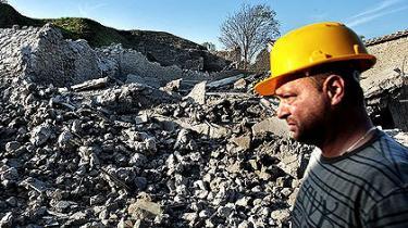 En redningsarbejder passerer den sammenstyrtede gladiatorsal i Pompeji.