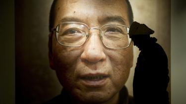 Den kinesiske systemkritiker og fredsprismodtager Liu Xiaobo passeres af en hueklædt mand i Oslos Fredspris Center. Dagens æresgæst må forblive i sin kinesiske fængselscelle på 11. år, ligesom hverken hans kone eller to brødre har fået udrejsetilladelse. Det vil betyde, at selve prisen ikke kan overrækkes, da ingen kan møde op og modtage den. Kina er rasende over, at fredsprisen går til én, de betegner som 'kriminel', og de har truet både lande og personer, som vover at møde op til ceremonien i dag.