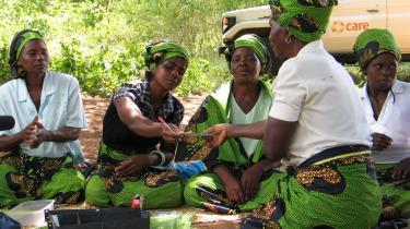 Kasseren for en spare-låne-gruppe i Mozambique rækker en deltagers bankbog tilbage, efter at hun har indbetalt sit ugentlige indskud, og det er blevet omhyggeligt noteret i hele gruppens påsyn.