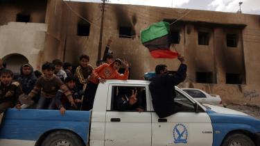 Medlemmer af Libyens politistyrker kører rundt i gaderne i den oprørskontrollerede, østlige libyske by Tobruk med børn på ladet og flager med landets nationalflag indtil 1969, da Gaddafi indførte et helt ensfarvet grønt flag.