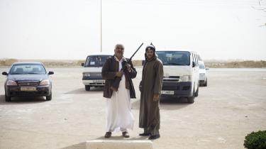 To mænd i Tobruk, en by, der er overtaget af oprørere, står foran biler, der bliver brugt af libyske unge til at transportere udenlandske journalister.