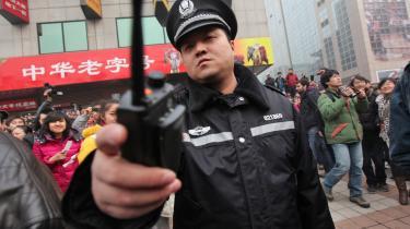 I Beijings Wangfujing-distrikt spreder en kinesisk politimand demonstranter og journalister, der mødes efter anonyme opfordringer på internettet til en 'kinesisk jasmin-revolution'.