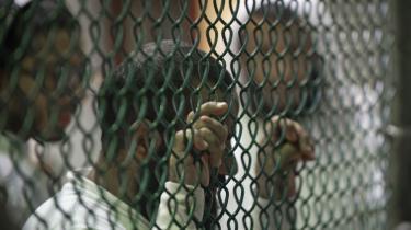Tilbageholdte fanger står i kø ved et hegn og venter på biblioteksbøger i Guantánamo Bays Camp VI.