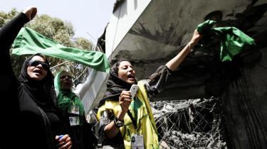 Libyske kvinder vifter med det libyske flag for at vise deres støtte til Muammar Gaddafi uden for den bygning i Tripoli, som NATO-fly ramte med missiler i weekenden. Ved angrebet blev blandt andet Gaddafis søn Said-Arab Gaddafi dræbt, mens Muammar selv overlevede angrebet, selv om han også opholdt sig i bygningen.