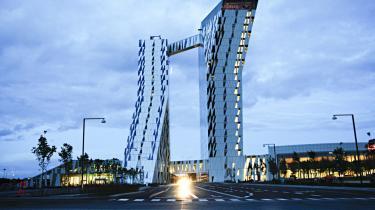 Sky-tårnet er knækket over og viftet ud, så de to 'indre' facader ikke tager hinandens view. Med fælles foyer i bunden og den listige kyssenes bro i de   højere luftlag.