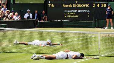 Novak Djokovic (bagest) og Jo-Wilfried Tsonga gav tilskuerne en gedigen tennisoplevelse, da de fløj rundt på banen i tre timer — og efter en opvisning i tennisakrobatik begge landede fladt på Wimbledons græs. Djokovic vandt opgøret og skal spille finale i morgen, søndag, mod Rafael Nadal.