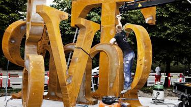 Det store T i skulpturen står for Turèll. D for Dan er derimod nede i et langt mindre format, angiveligt fordi skulptøren synes, det ikke egner sig til den store størrelse. Den rustne overflade på stålet gør skulpturen vejrbestandig. Rundt om skal der være en 47 meter lang, trekantet, grøn bænk — en meter for hver af digterens leveår. Det er tilladt for børn at lege på bogstaverne.