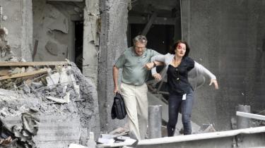 Kvarteret omkring den norske regeringsbygning var som en krigszone i går eftermiddag. Alle ruder var blæst ud af eksplosionen, røg bølgede mod himlen, blødende mænd og kvinder vaklede ud af den store bygning, én livløs person hang ud af et vindue. 'Folk gik rundt på hovedgaden foran regeringsbygningen i chok, grædende,' siger øjenvidnet Erlend Grøner Krogstad til Information. Antagelsen var fredag aften, at bomben bag ødelæggelserne var anbragt et sted inde i regeringskvarteret.
