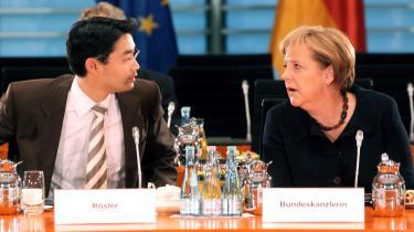 Koalitionsparterne Philipp Rösler (FDP) og Angela Merkel (CDU) er helt uenige om, hvordan den tyske regering skal håndtere krisen i Grækenland.