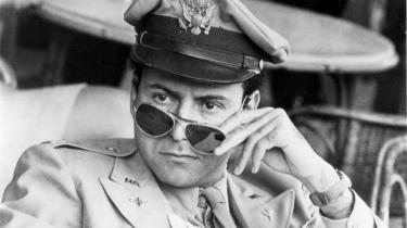 Unik. Joseph Hellers hovedperson, den dødsangste bombepilot Yossarian – her i skikkelse af Alan Arkin i filmatiseringen fra 1970 – blev få år efter udgivelsen en kultfigur for ungdomsoprørets krigsmodstandere.