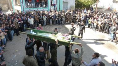 Demonstranter i byen Homs kaster ris på Abdul Haleem Baqours kiste. 12.000 soldater omringer nu byen og får FN til at frygte for en massakre.