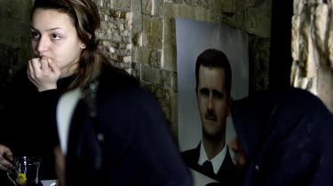 Kvinder på cafe i Damaskus følger Syriens præsident, Bashar al-Assads tv-transmitterede tale den 10. januar. I talen lovede han at knuse den opstand, der siden dens udbrud er blevet stadig mere blodig og militariseret.
